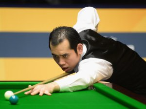 Dechawat Poomjaeng beat Stephen Maguire to reach the second round of the World Championship.